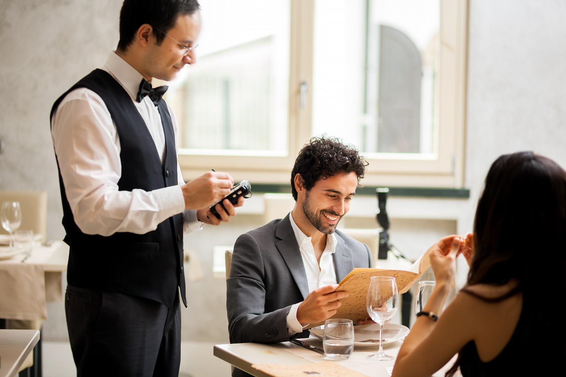 Camarero de restaurante usando comandero electrónico